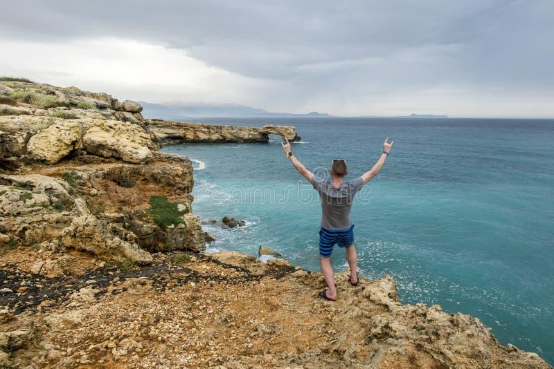 L'homme se tient au bord d'une falaise et des regards dans la distance en mer photos stock