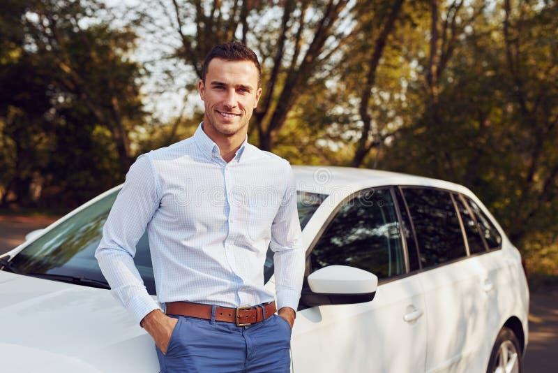 L'homme se tient devant sa nouvelle voiture photographie stock