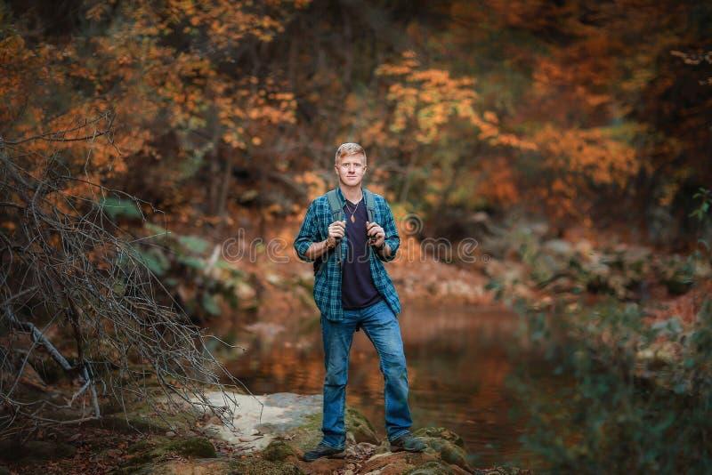 L'homme se tient pr?s du courant de montagne en automne image stock