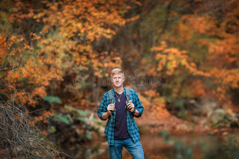 L'homme se tient pr?s du courant de montagne en automne images stock