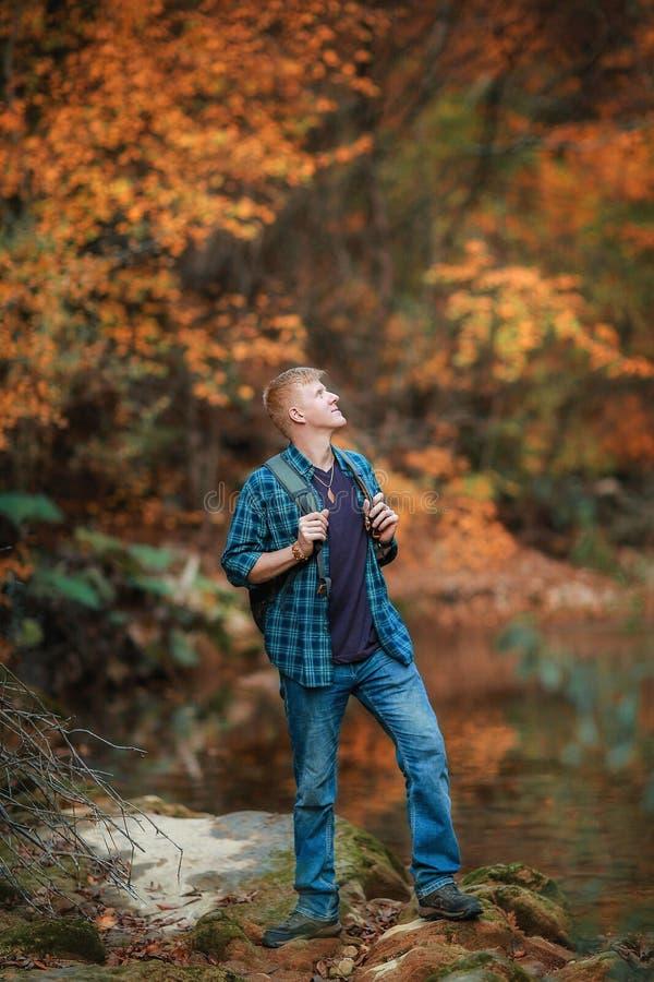 L'homme se tient pr?s du courant de montagne en automne image libre de droits