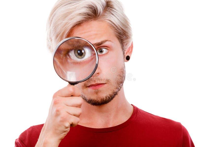 L'homme se tient sur la loupe d'oeil regardant par la loupe photo libre de droits