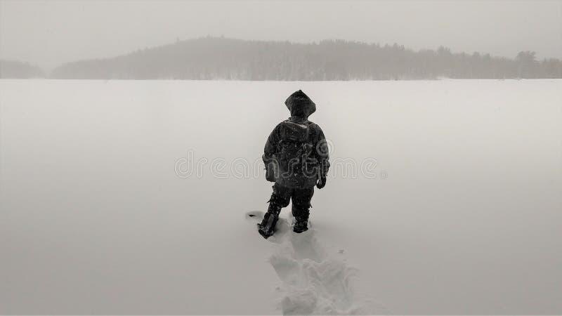 L'homme se tient sur le lac congelé dans la tempête de neige photographie stock