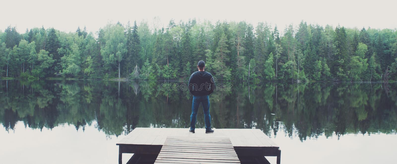 L'homme se tient sur le pilier d'un beau lac, photo panoramique Le concept de la libert? et de l'ind?pendance images libres de droits