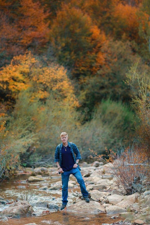 L'homme se tient sur les pierres dans le courant de montagne image libre de droits