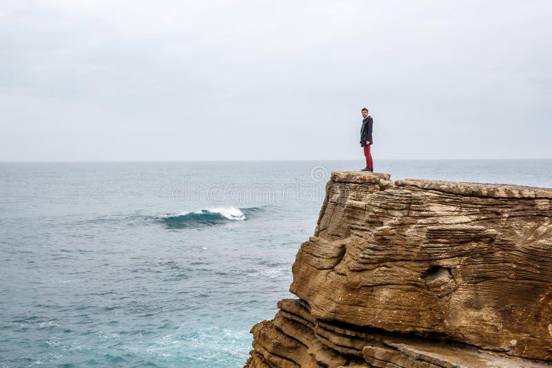 L'homme se tient sur une falaise de mer, examinant la distance sur une mer orageuse foncée photographie stock libre de droits