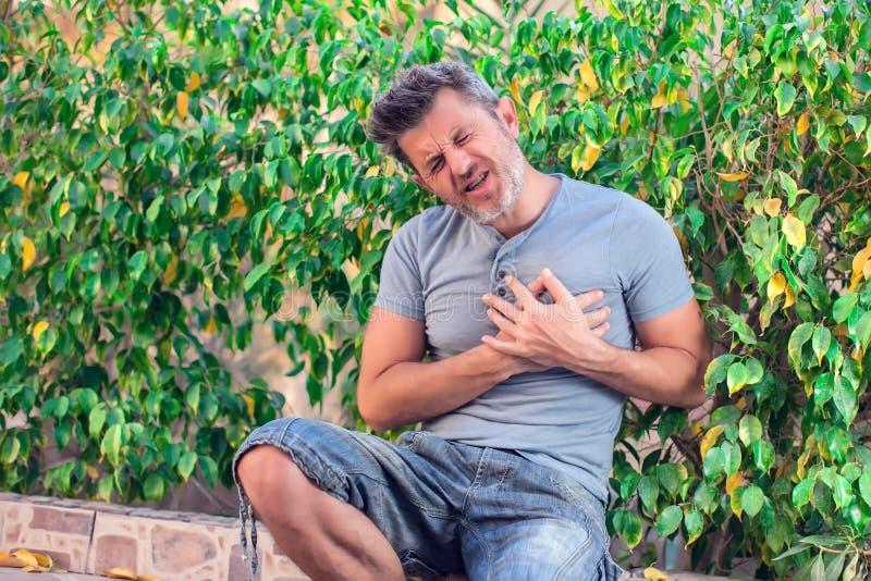 L'homme sent la crise cardiaque forte extérieure Concept de personnes, de soins de santé et de médecine photographie stock libre de droits
