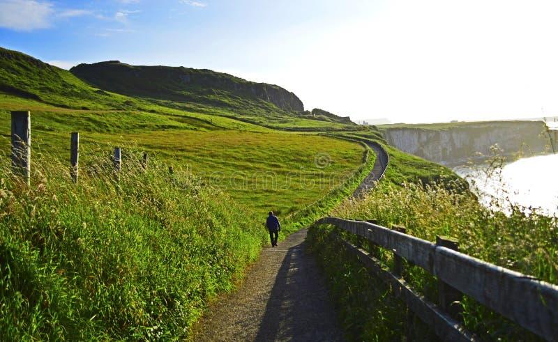 L'homme seul marche au sentier piéton de littoral, R-U photos stock