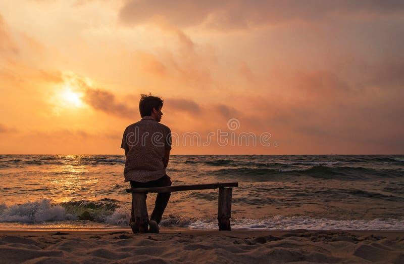 L'homme seul s'assied sur un banc sur la côte appréciant le coucher du soleil photographie stock libre de droits