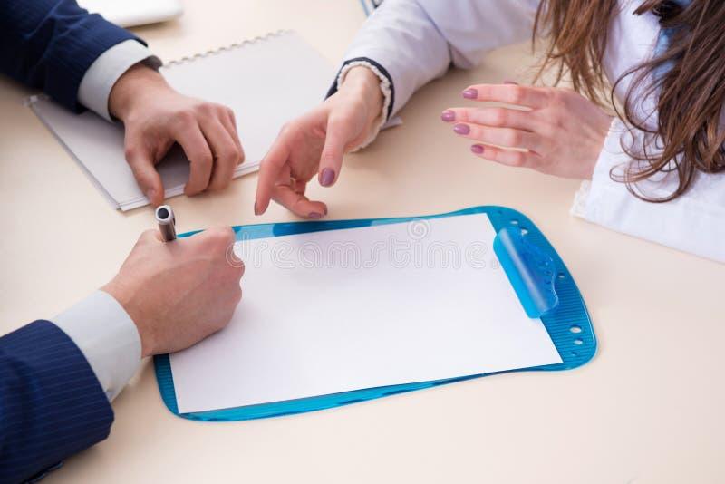 L'homme signant le contrat d'assurance-maladie image stock
