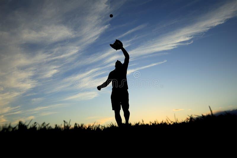 L'homme silhouetté par le coucher du soleil commence juste image libre de droits