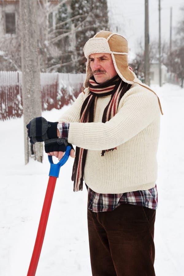 L'homme sombre nettoie la neige photo libre de droits