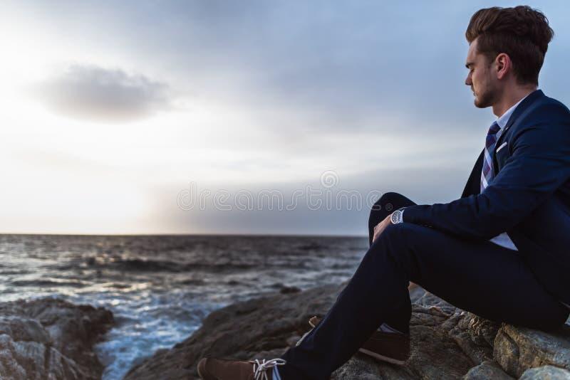 L'homme songeur dans le costume s'assied sur les roches près de la mer et de la pensée Jeune type photos stock