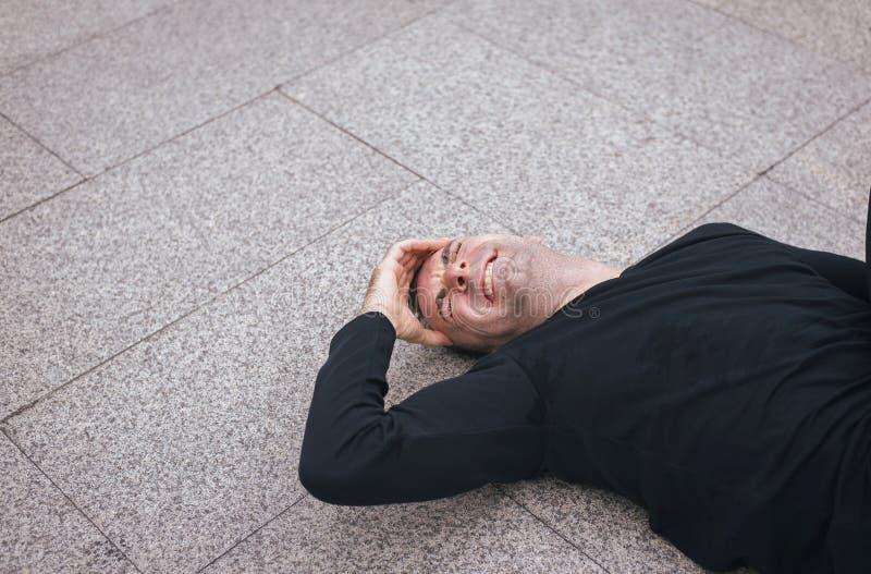 L'homme souffrant de la douleur ont une blessure de mal de tête et tombent vers le bas sur le plancher après séance d'entraînemen photographie stock libre de droits