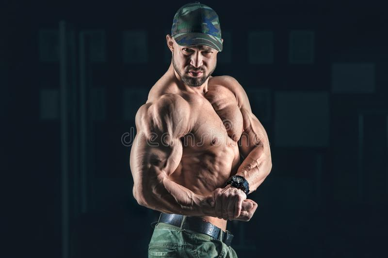 L'homme sportif de bodybuilder fort pompant muscles le bodyb de séance d'entraînement photo stock