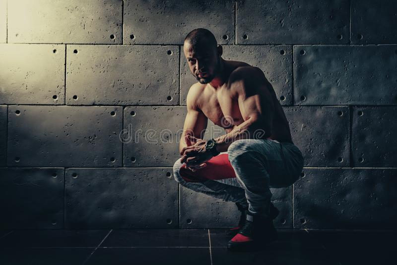 L'homme sportif de bodybuilder fort pompant muscles le bodyb de séance d'entraînement photographie stock