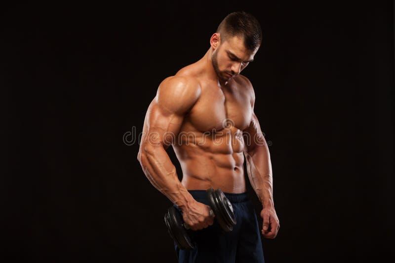 L'homme sportif de puissance belle avec l'haltère regarde avec confiance en avant Bodybuilder fort avec six paquets, ABS parfait images libres de droits