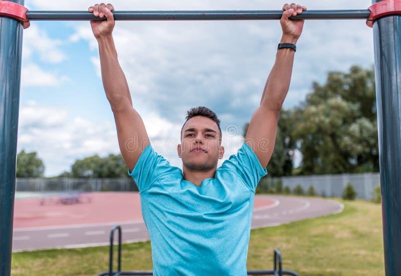 L'homme sportif en été dans la ville, tire vers le haut sur la barre, une séance d'entraînement saine de forme physique de mode d photo libre de droits
