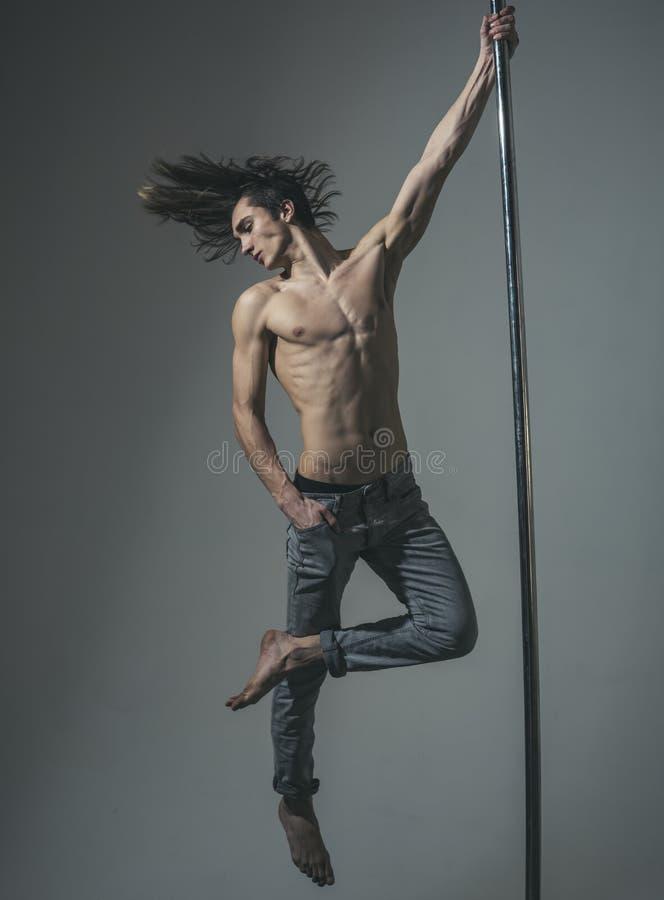 L'homme sportif font les éléments acrobatiques sur le pylône dieting séance d'entraînement macho sexy de danseur sur le poteau Tr photographie stock libre de droits
