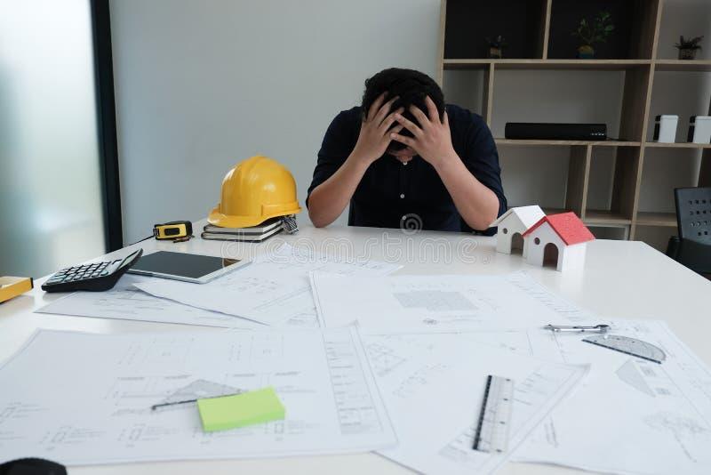 L'homme stressant d'ingénieur a mis la main sur la tête l'architecte épuisé est photo stock