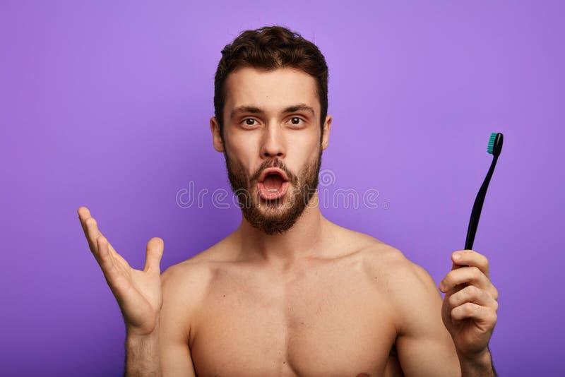 L'homme stupéfait avec la bouche largement ouverte, regards fixes à la caméra, tient la brosse à dents à disposition photos stock