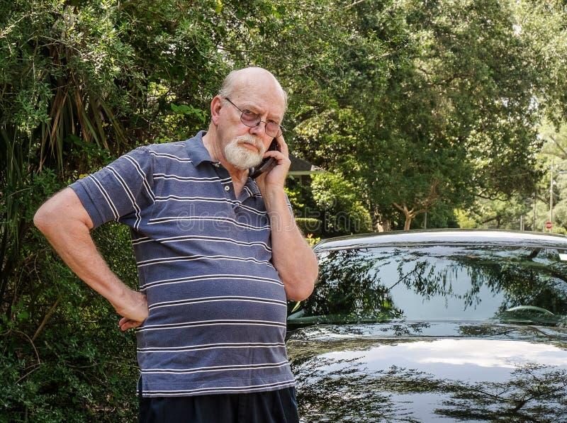 L'homme supérieur au téléphone portable dans la route à côté de la voiture réclame l'aide photos libres de droits