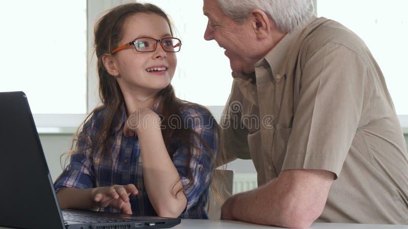 L'homme supérieur et sa petite-fille observent quelque chose sur l'ordinateur portable photographie stock libre de droits