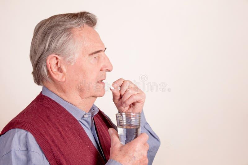 L'homme supérieur prend la pilule avec le verre de l'eau photographie stock