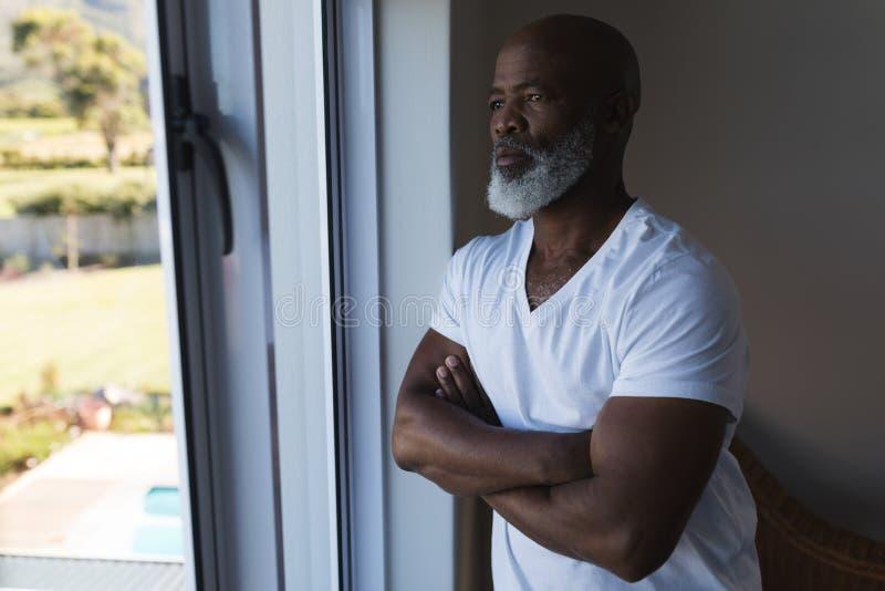 L'homme supérieur regardant par la fenêtre avec des bras a croisé à la maison images stock
