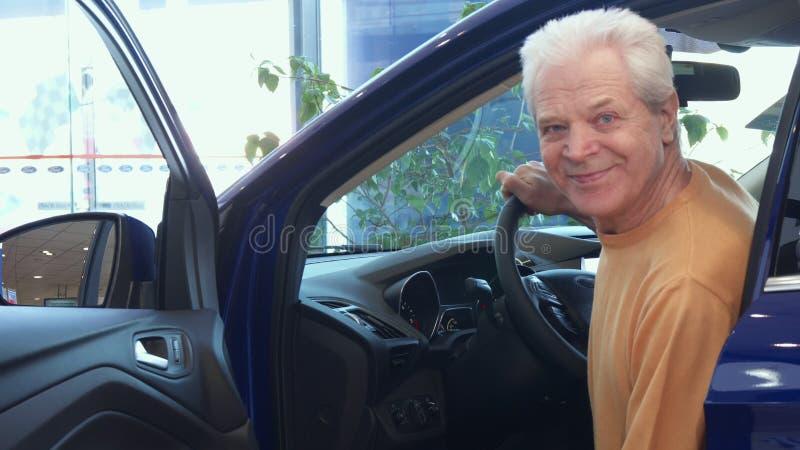 L'homme supérieur s'assied dans la voiture au concessionnaire images libres de droits