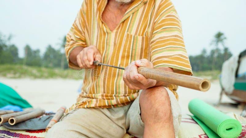 L'homme supérieur s'assied sur la plage et cannelure de fabrication à la main, plan rapproché photographie stock