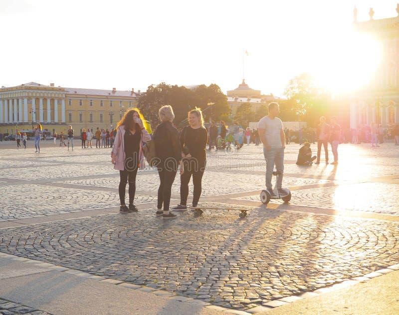 L'homme sur Gyroscooter Les gens sur Gyroscooter montent au coucher du soleil sur la place de palais, parmi les touristes à St Pe photo libre de droits