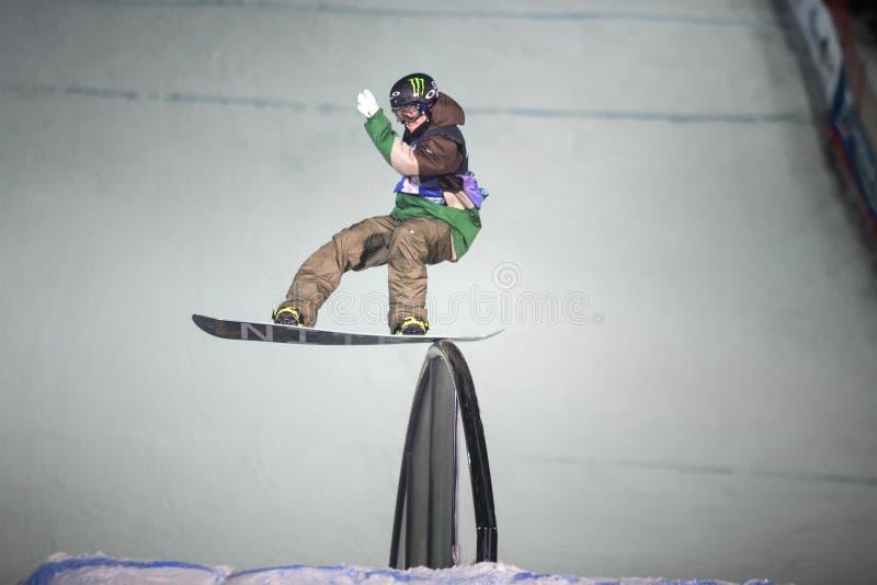 L'homme sur le surf des neiges glisse sur le rail photographie stock
