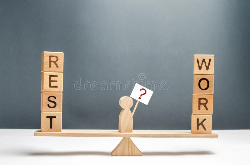L'homme sur les échelles avec une affiche et un signe des questions Le choix entre le travail et le concept de repos du bon équil image stock