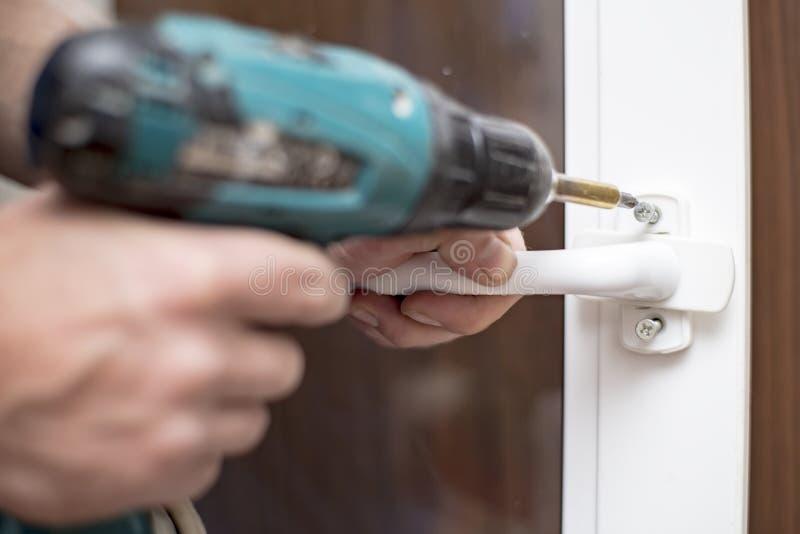 L'homme tient dans des ses mains un tournevis électrique et va visser la poignée sur la fenêtre de PVC image stock