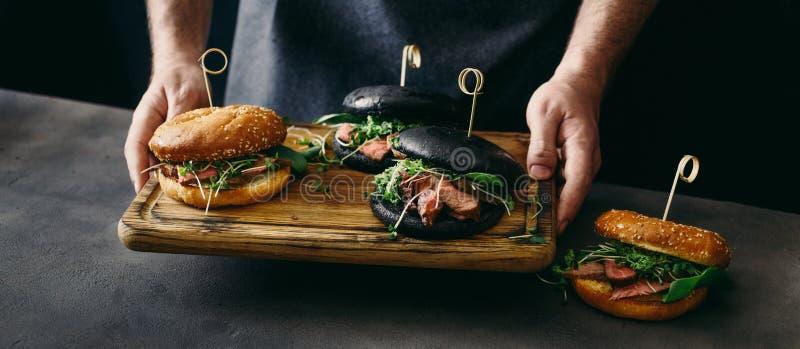 L'homme tient différents hamburgers de conseil avec de la viande grillée de boeuf image libre de droits
