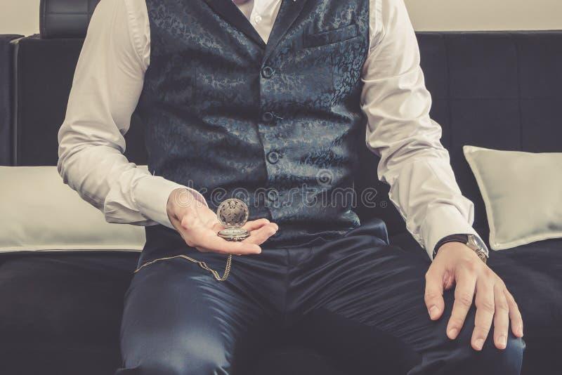 L'homme tient la montre de poche dans sa main photos libres de droits