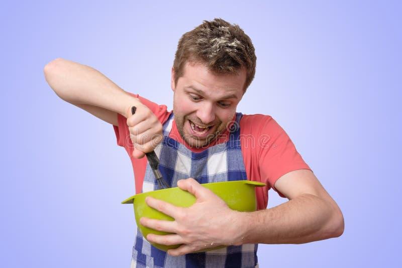 L'homme tient la vaisselle de cuisine faisant cuire avec le visage curieux image stock