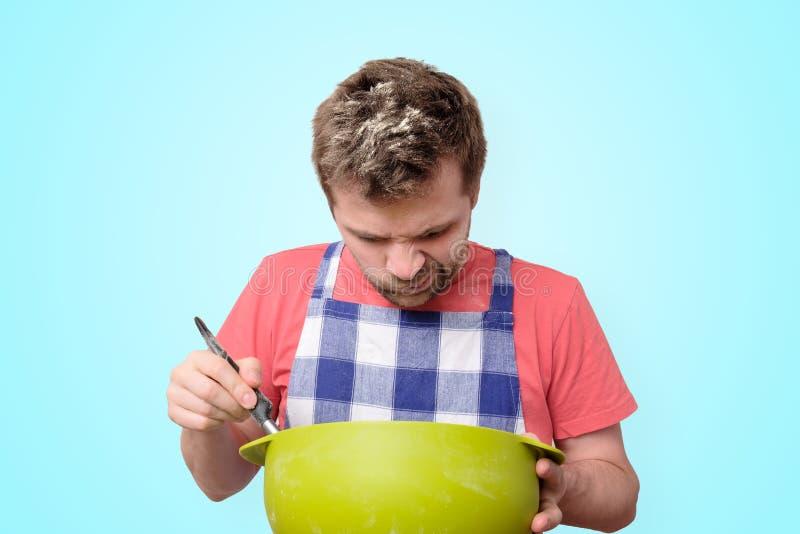 L'homme tient la vaisselle de cuisine faisant cuire avec le visage curieux photographie stock