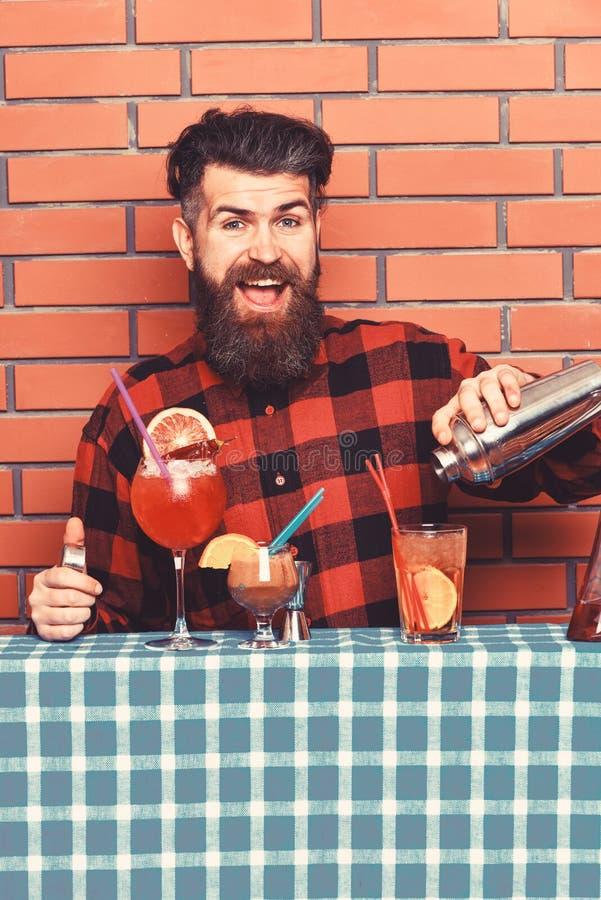 L'homme tient le dispositif trembleur sur le fond de mur de briques Le barman avec la barbe et le visage heureux fait le cocktail image libre de droits