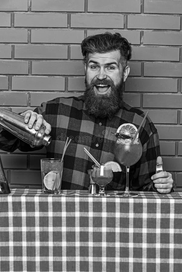 L'homme tient le dispositif trembleur sur le fond de mur de briques Le barman avec la barbe et le visage heureux fait le cocktail images stock