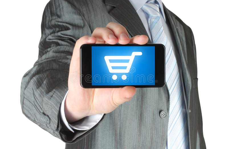 L'homme tient le téléphone intelligent avec le caddie photographie stock