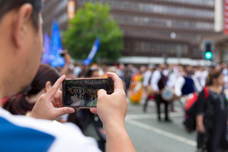 L'homme tient le téléphone intelligent et la vidéo de enregistrement photographie stock libre de droits