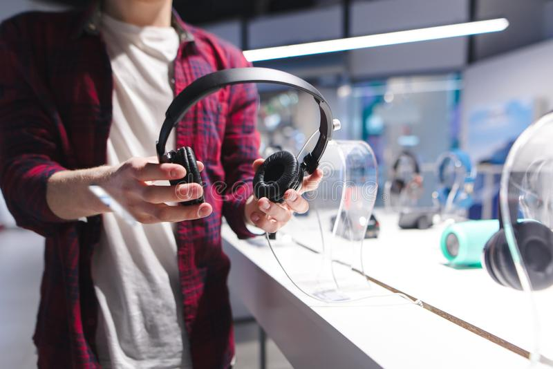 L'homme tient les écouteurs noirs à l'arrière-plan du magasin Écouteurs de achat dans un magasin de technologie photos libres de droits