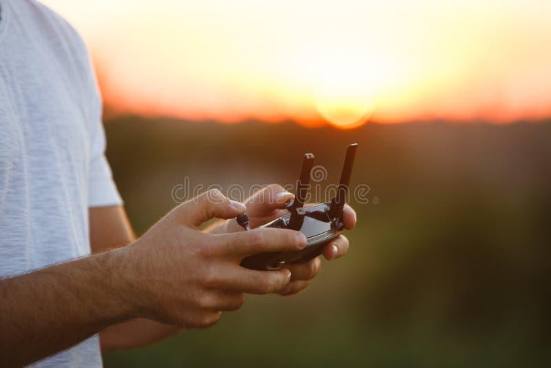 L'homme tient un contrôleur à distance de bourdon dans des ses mains Plan rapproché du quadrocopter RC pendant le vol Le pilote p photographie stock libre de droits