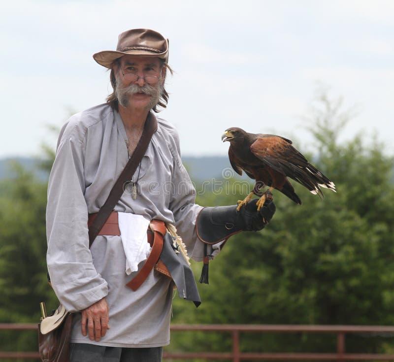 L'homme tient un faucon pendant une démonstration de fauconnerie photo libre de droits