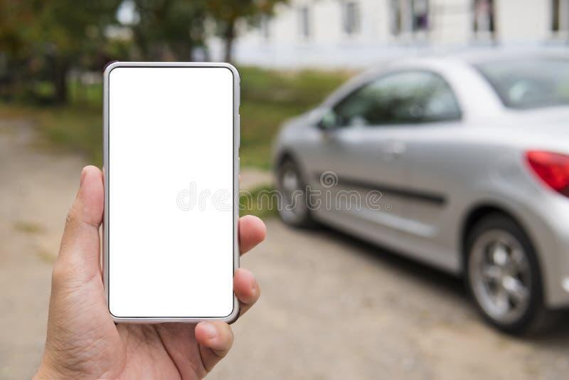 L'homme tient un smartphone vide-sreen dans la main gauche près du véhicule garé Personne dans le lien de voiture d'utilisations  image libre de droits