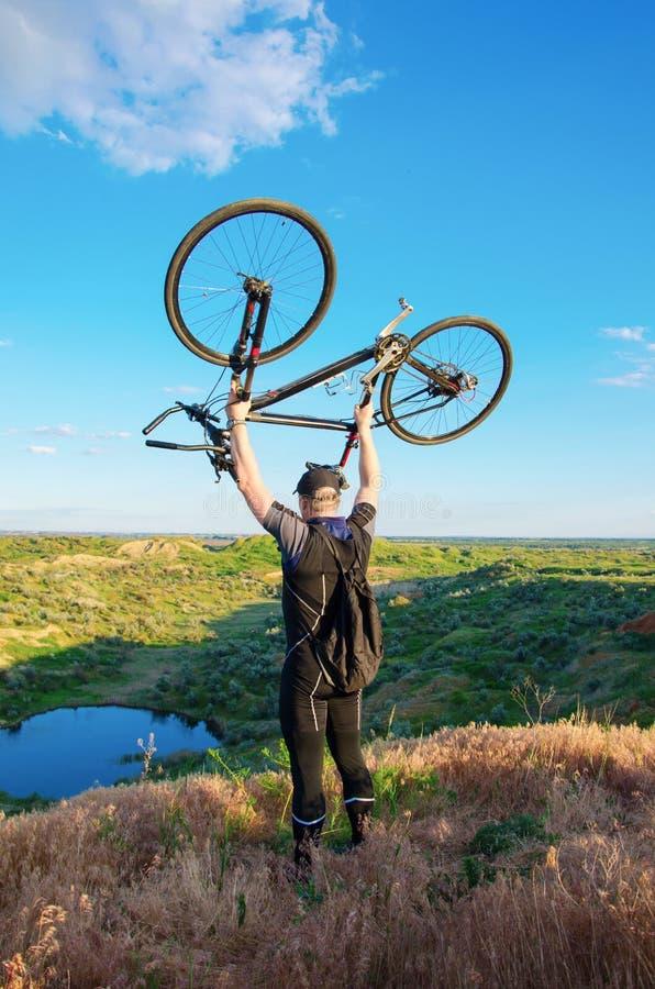 L'homme tient une bicyclette au-dessus d'une tête image libre de droits