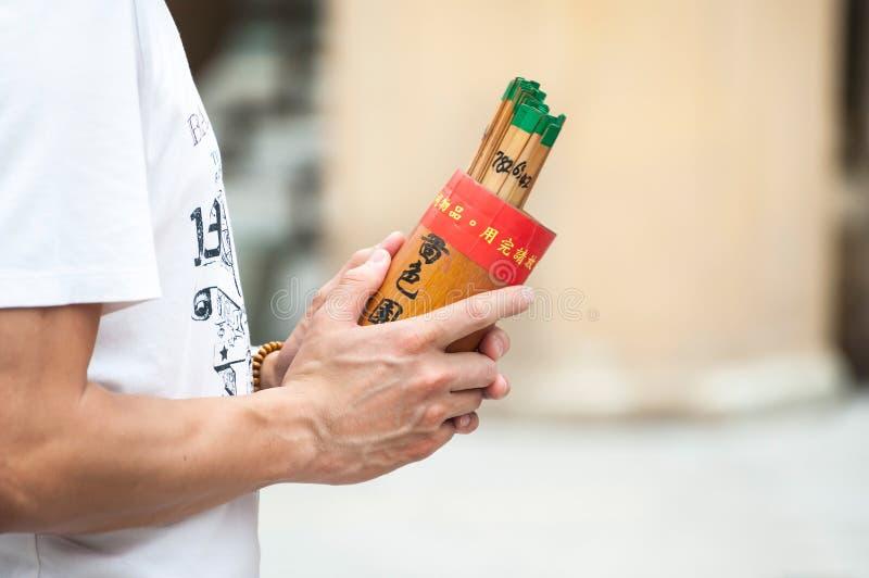 L'homme tient une boîte de bâtons de fortune chez Wong Tai Sin Temple, Hong Kong images stock