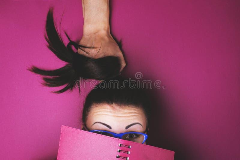 L'homme tire les cheveux du ` s de fille quand elle lit le carnet photographie stock